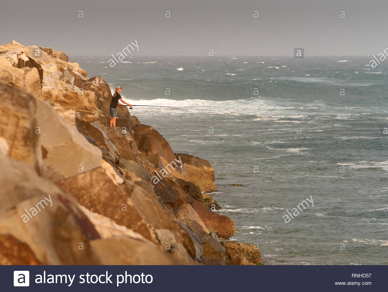 Yamba, NSW / Australia - February 12 2019: A young rock-fisherman, casting his line into the Pacific Ocean, from the large rocky breakwall he's on. - Stock Image