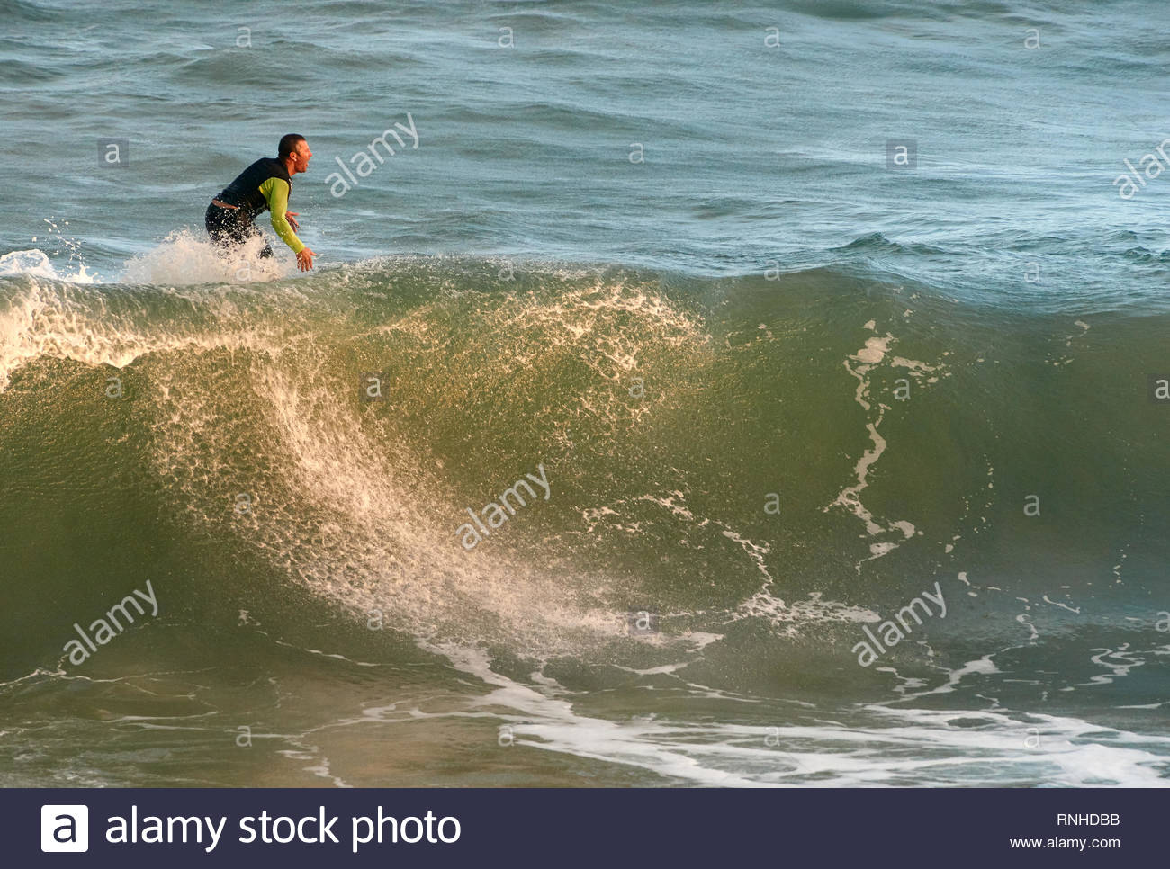 A Caucasian male surfer, kook, expressing happy dissatisfaction on his board, after just missing a nice wave at Turners Beach, Yamba, NSW, Australia. - Stock Image
