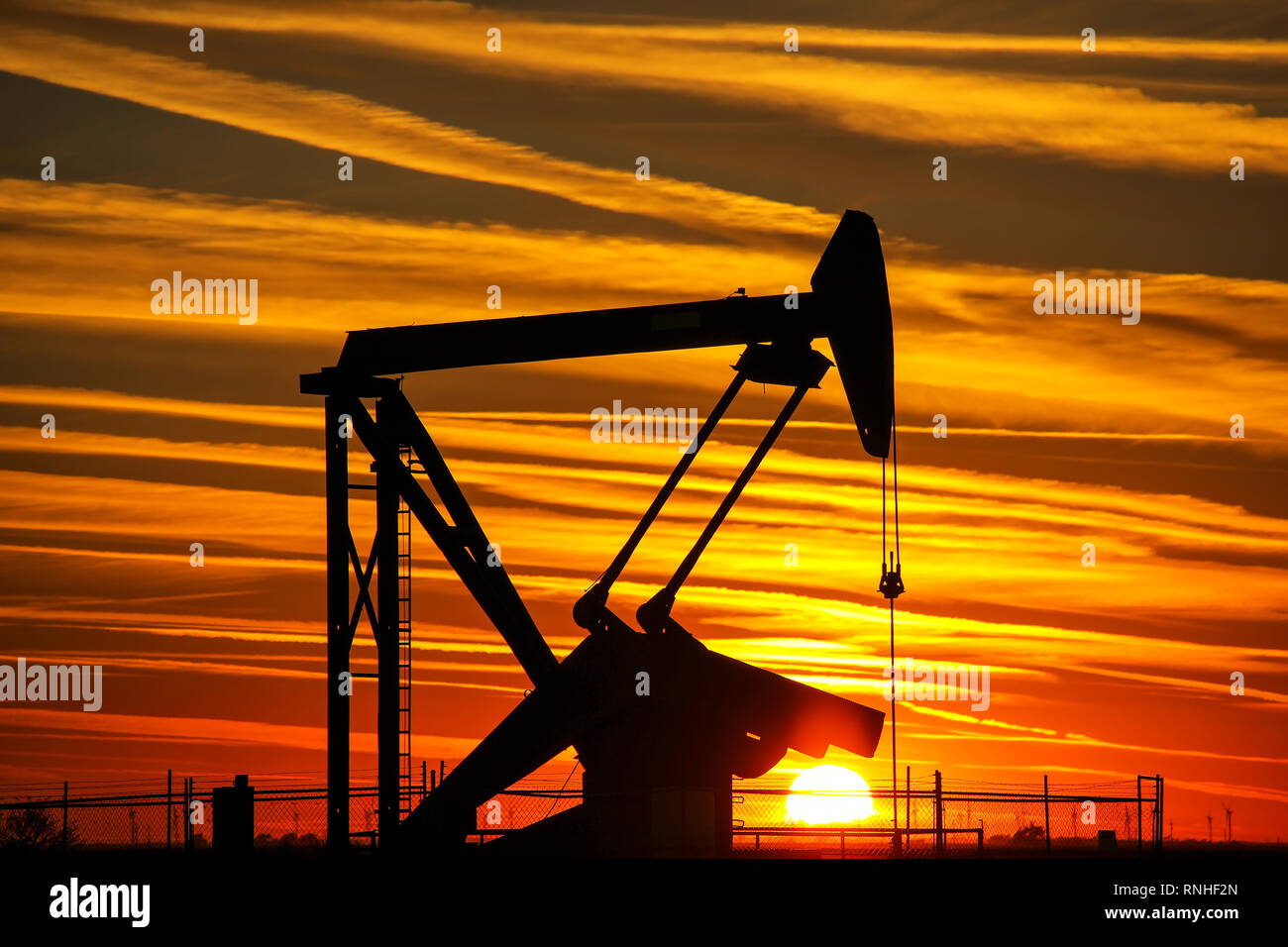 Silhouetted pump jack in the oil field at sunset - Stock Image