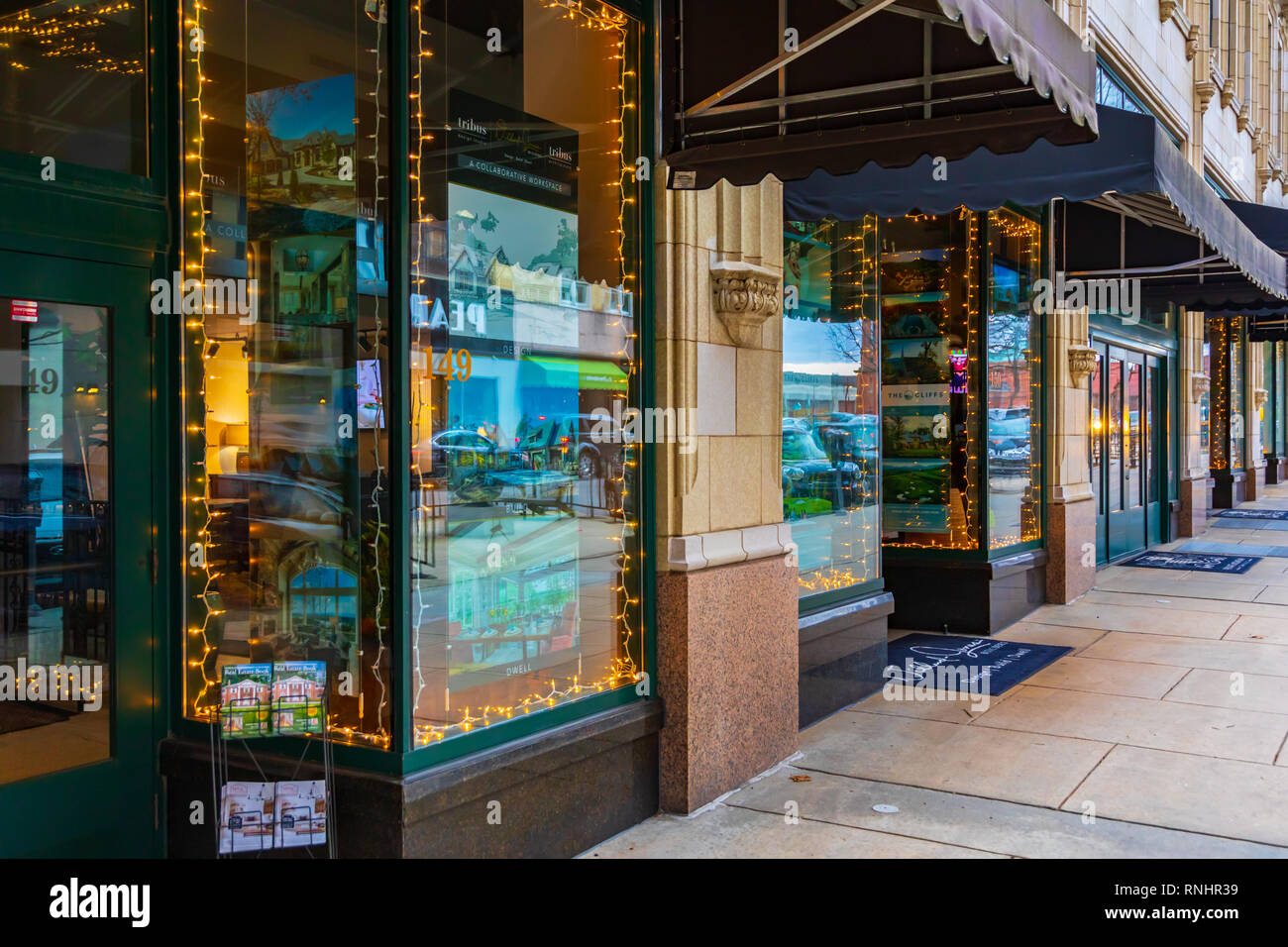 ASHEVILLE, NC, USA-2/16/19: Strings of lights and reflections fom the street shine in realtors' storefront windows along Page St. Stock Photo