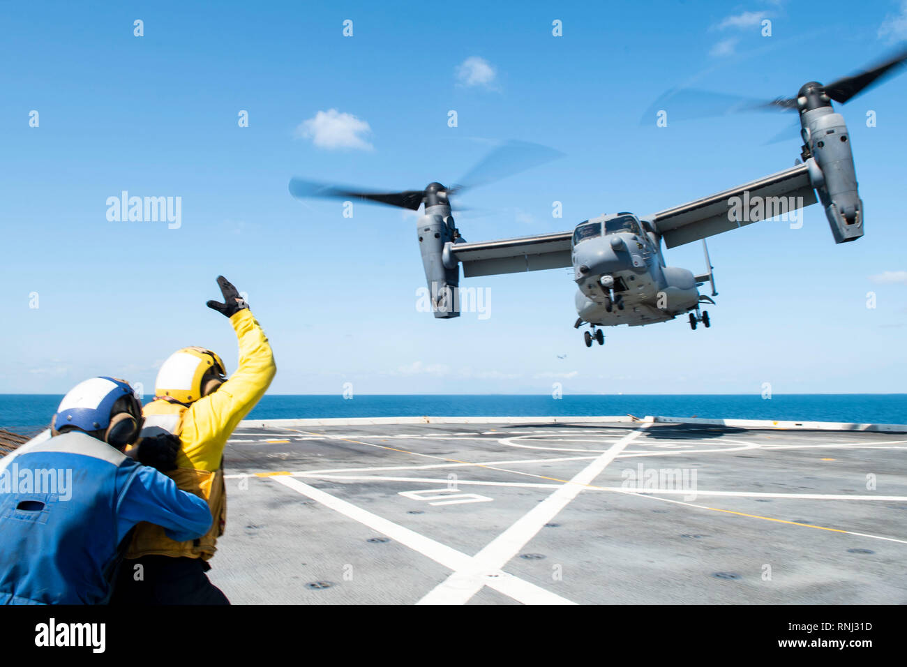 190218-N-DX072-1683 GULF OF THAILAND (Feb. 18, 2019) – Aviation Boatwain's Mate (Handling) 3rd Class Walter Rutherford, from Cheyenne, Wyo., signals to a CV-22 Osprey helicopter, assigned to the 353rd Special Operations Group, as it takes off from the flight deck of the amphibious transport dock ship USS Green Bay (LPD 20). Green Bay, part of the Wasp Amphibious Ready Group, with embarked 31st Marine Expeditionary Unit (MEU), is in Thailand to participate in Exercise Cobra Gold 2019. Cobra Gold is a multinational exercise co-sponsored by Thailand and the United States that is designed to advan - Stock Image