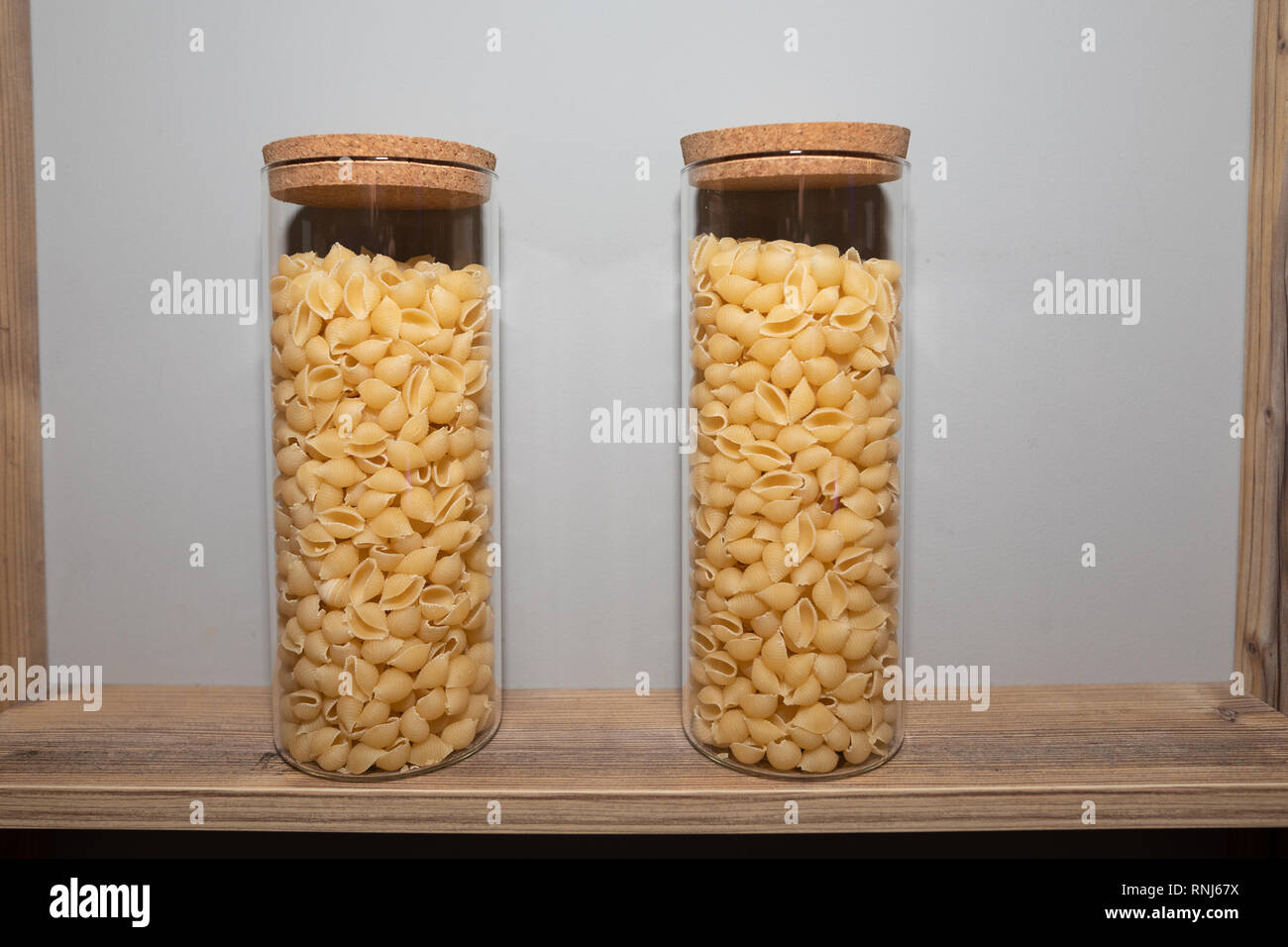two transparent jars of pasta are on the shelf - Stock Image