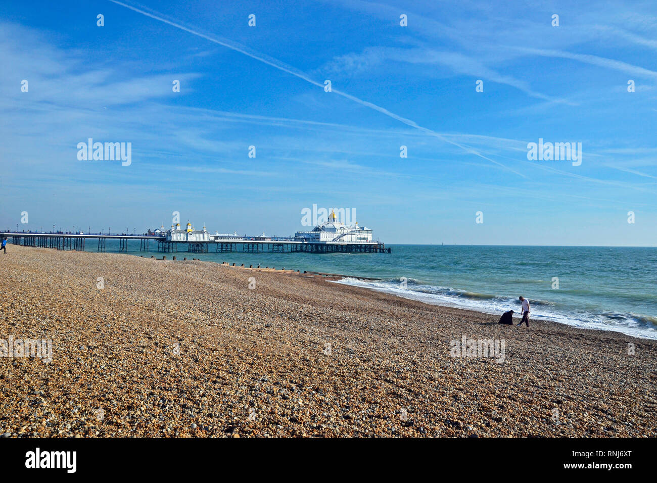 Eastbourne Pier, Eastbourne, East Sussex, UK. Brilliant sunshine brings people out to enjoy the seafront in February. View from the promenade. Stock Photo