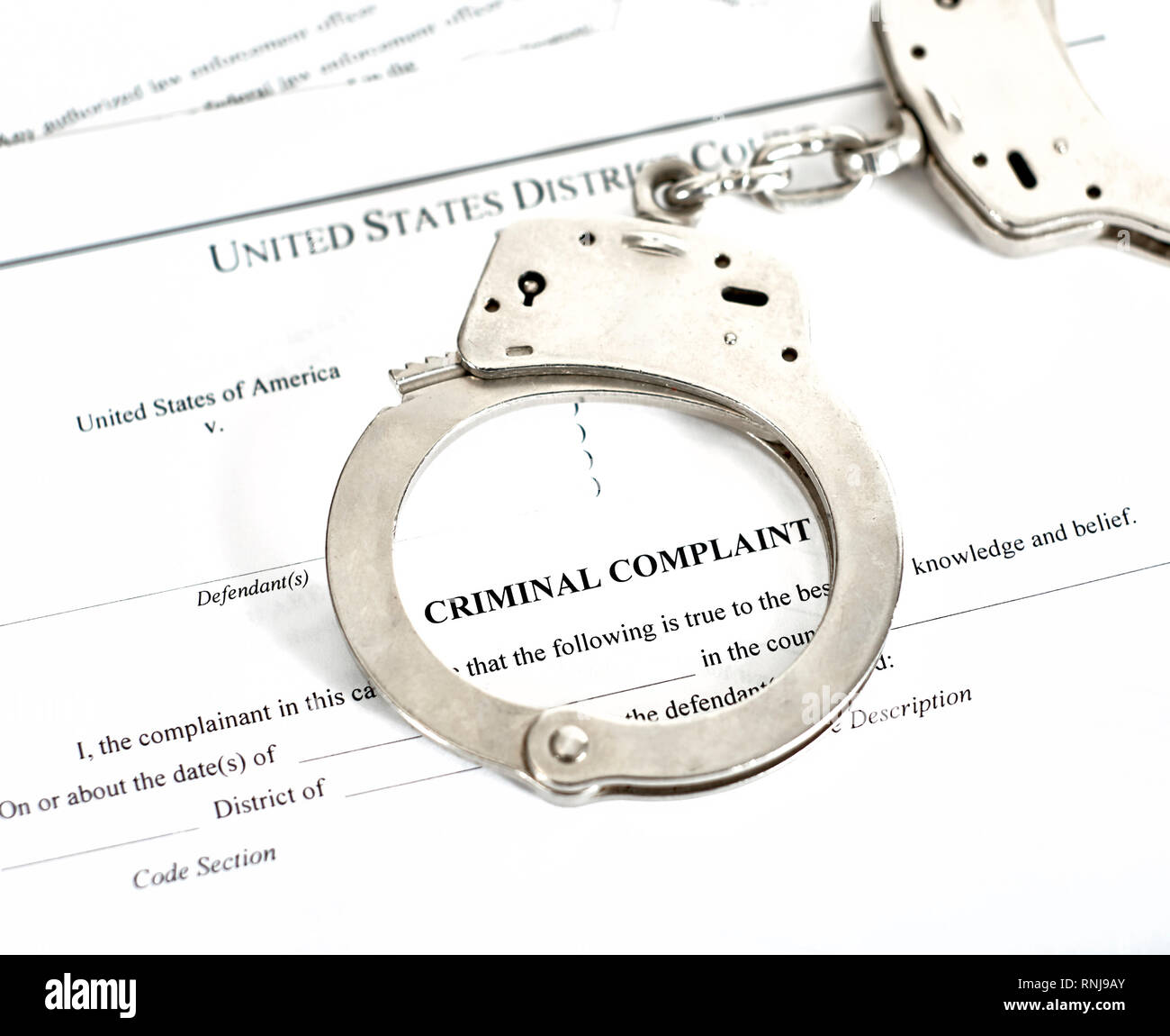 District Court criminal complaint, arrest warrant and search and seizure warrant doccuments with handcuffs isolated on white - Stock Image
