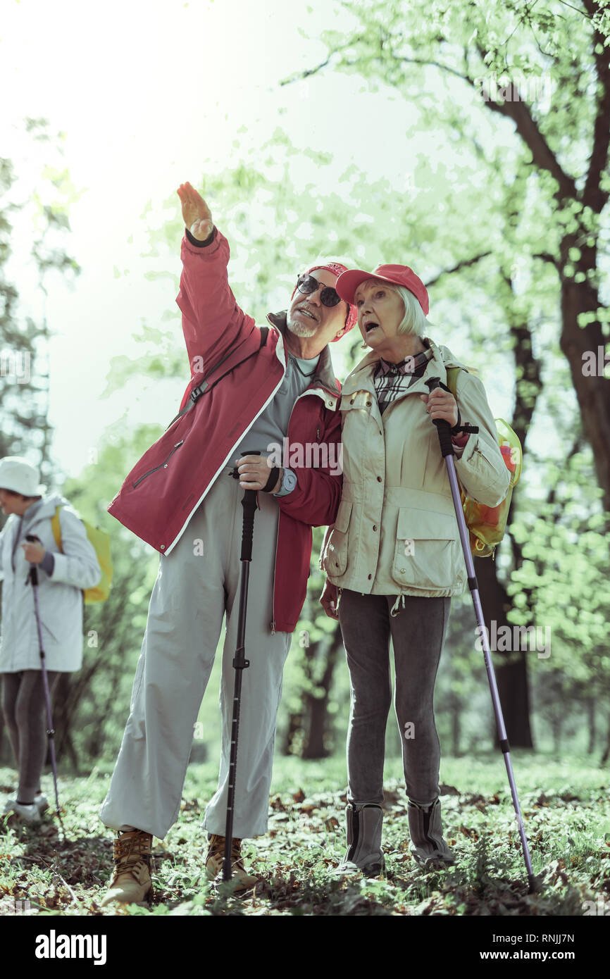 Couple of seniors looking at natural attractions while hiking - Stock Image