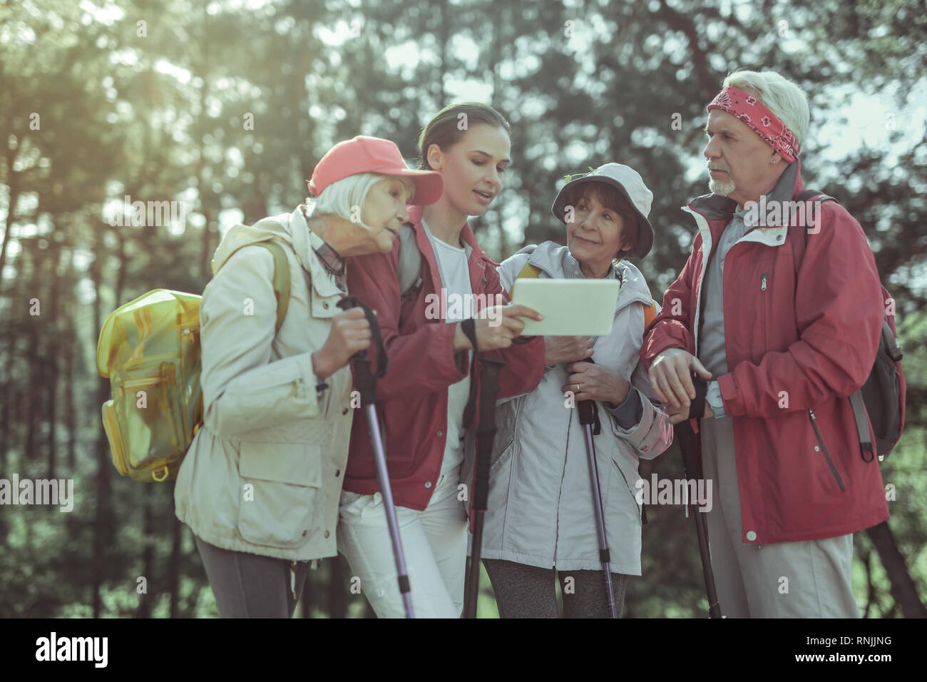 Group of tourists using interactive map for hiking - Stock Image