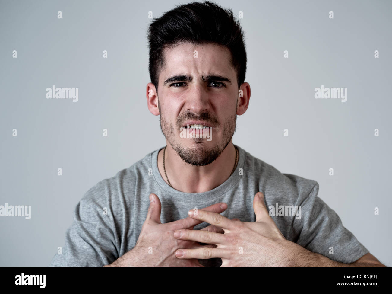 Close up portrait of young man with angry face feeling anger and looking upset at the camera. Human facial expressions, negative emotions and behavior Stock Photo