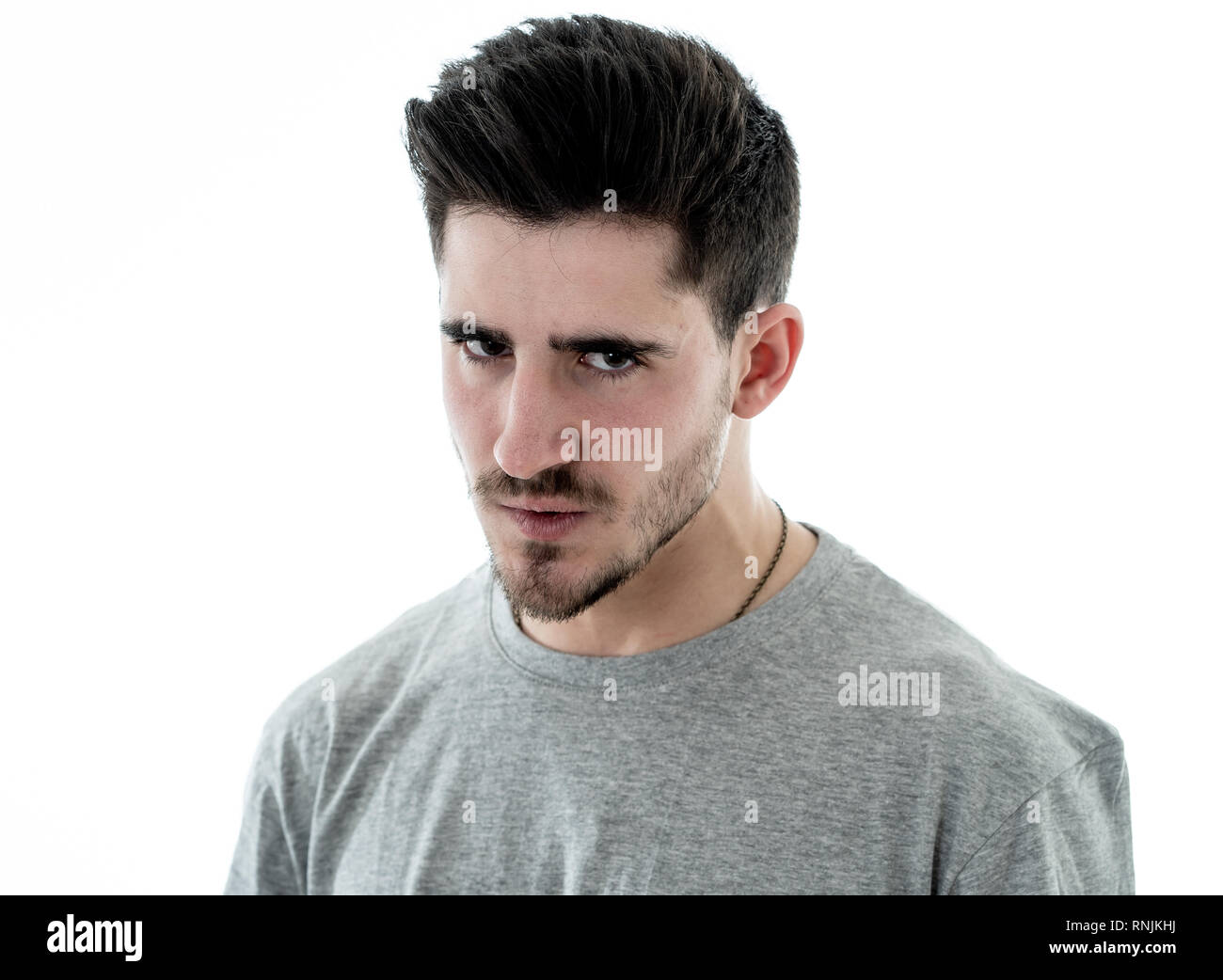 Close up portrait of young man with angry face feeling anger and looking upset at the camera. Human facial expressions, negative emotions and behavior - Stock Image