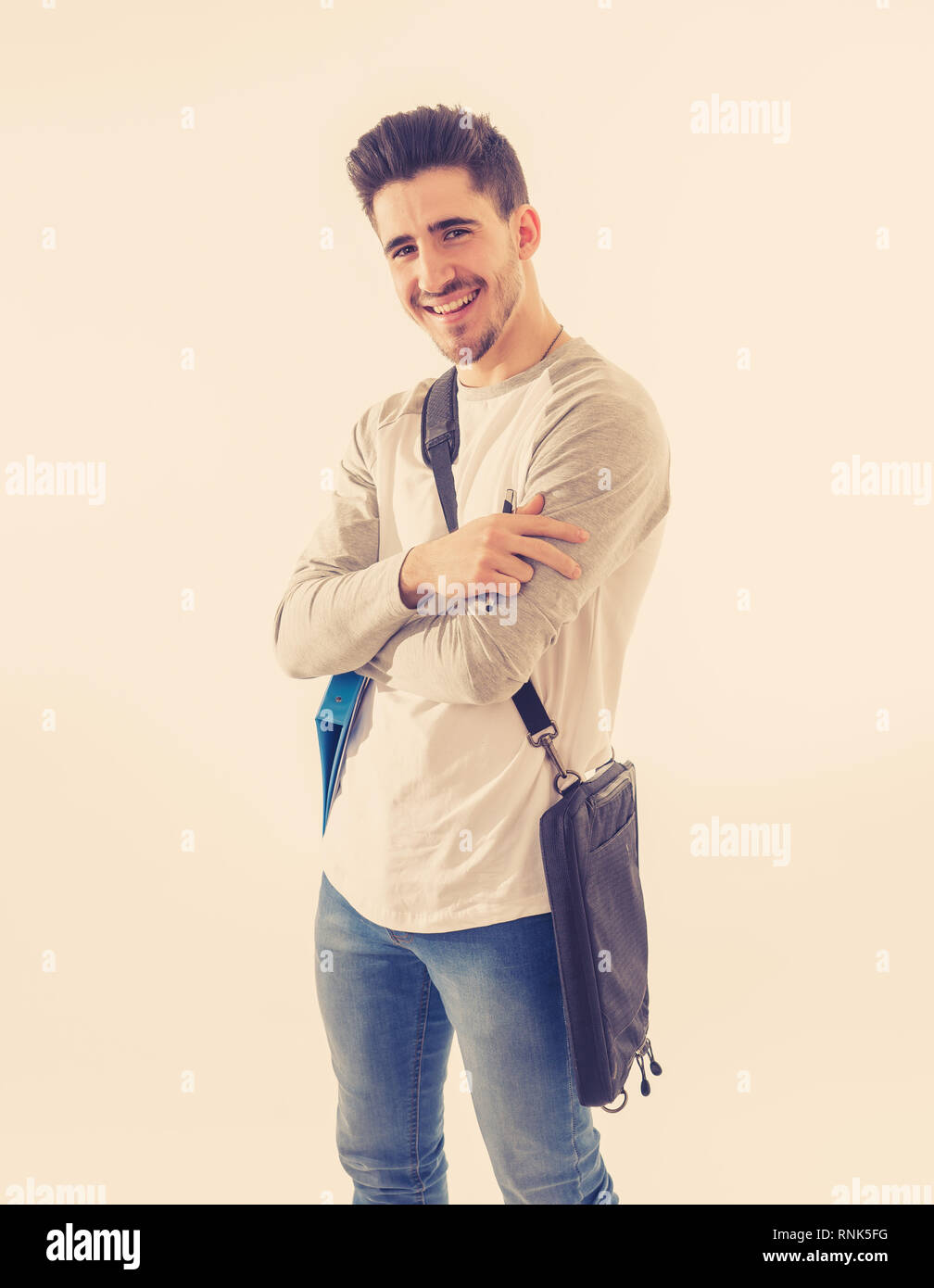 Portrait of Handsome college student man with backpack and notepad folder smiling against white background on his way to university lecture. in People - Stock Image
