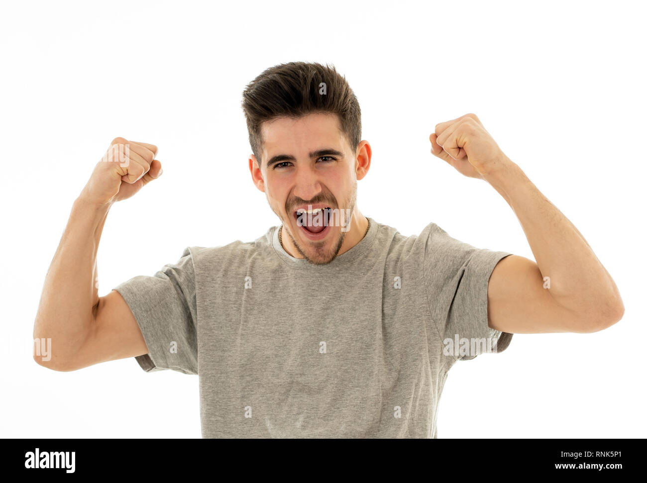 Portrait of young man celebrating achieving his goal, wining the lottery or having great success in face expression human emotions surprised and happy - Stock Image