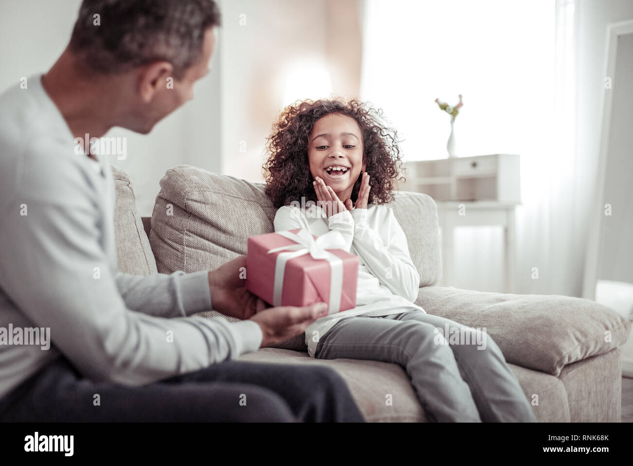 Happy little girl receiving a nice gift from her father - Stock Image