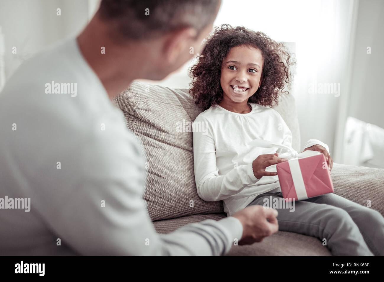 Excited careful father giving a nice present to a daughter - Stock Image