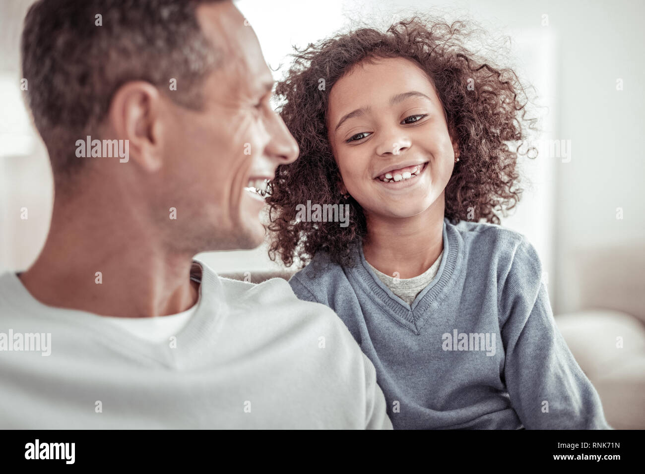 Joyful small girl spending good time with her father - Stock Image