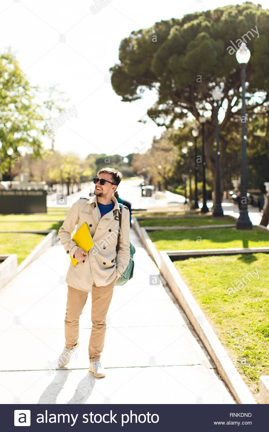 Young guy in beige coat is walking in sunny park with yellow laptop and bag. He is smiling to side. - Stock Image