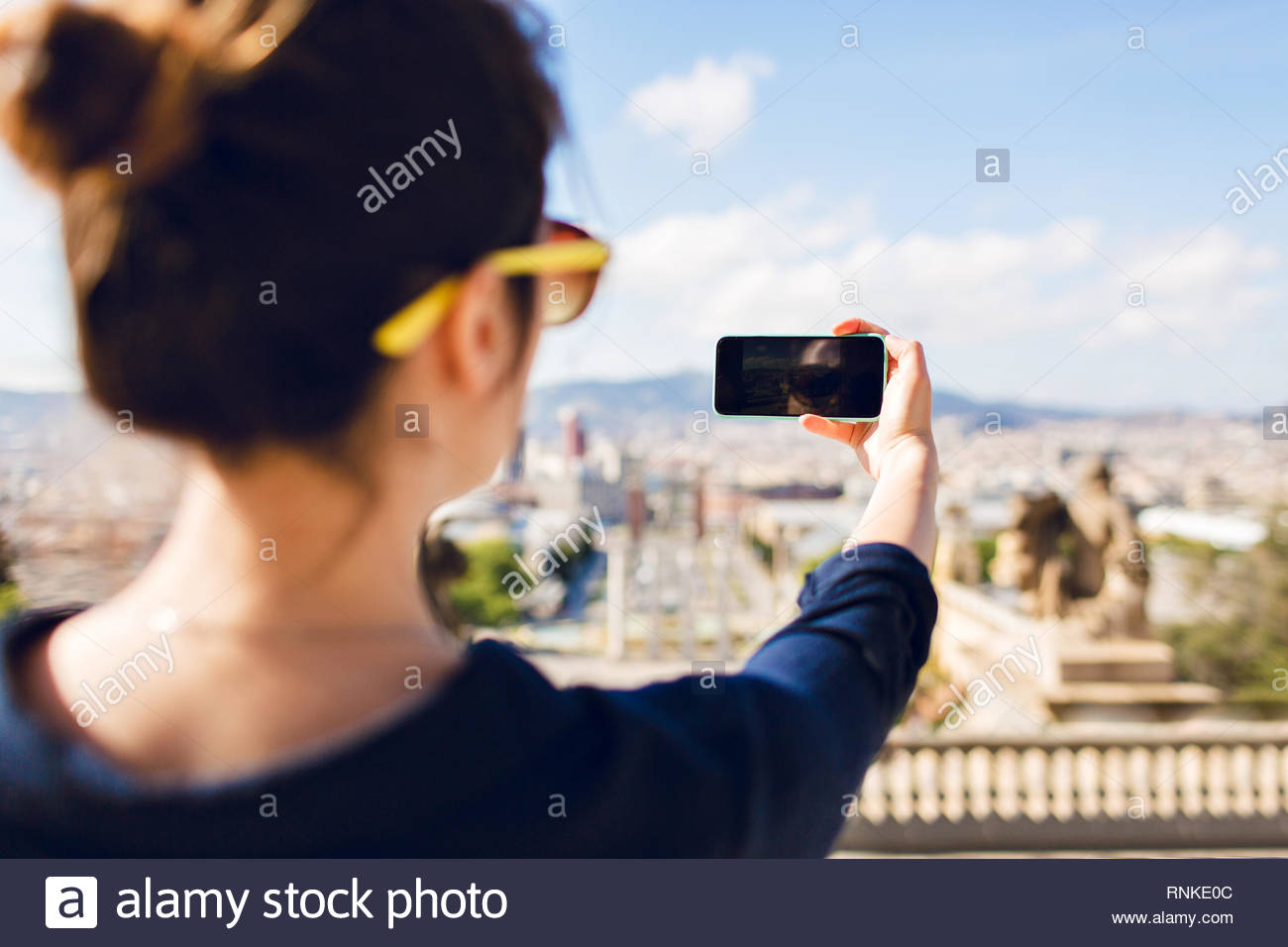 Back view of a girl in yellow sunglasses making photo of city from high. Focus on phone in hand. - Stock Image