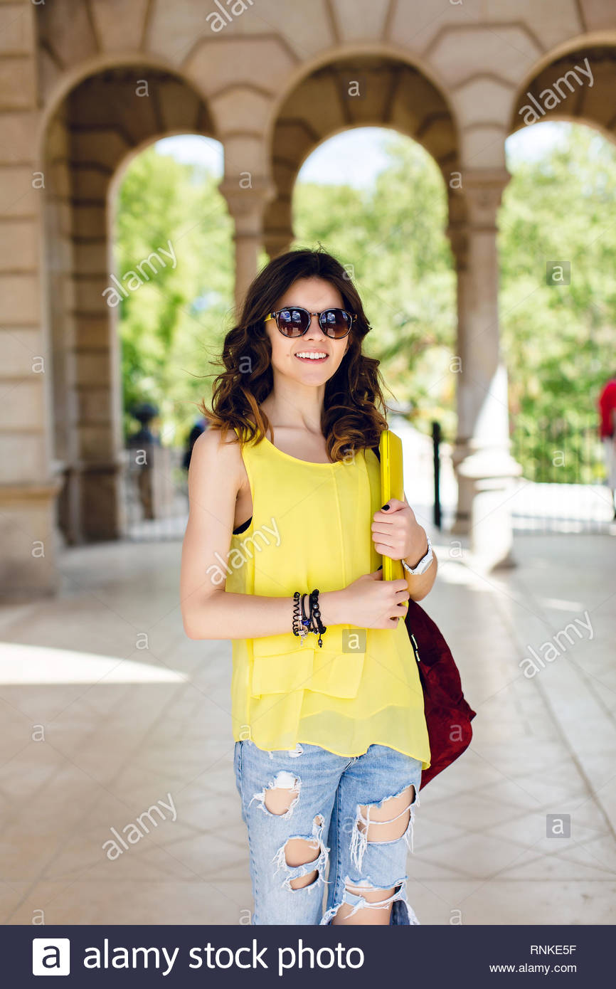 30cead5bcb Positive brunette girl in sunglasses is posing on archway background. She  wears yellow shirt