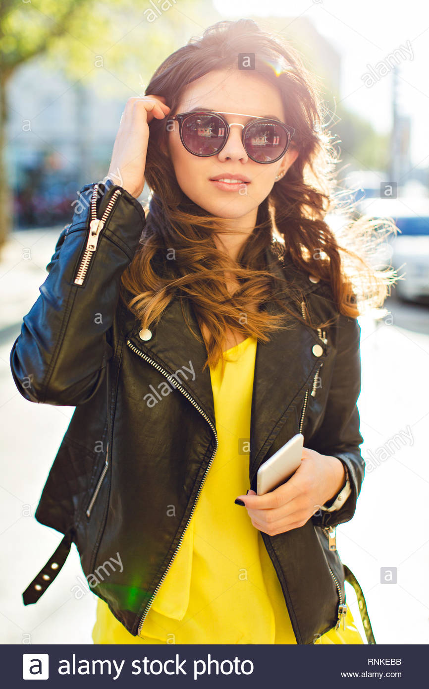 Portrait of pretty brunette girl posing to camera in sunglasses on street in sunny morning. She wears black jacket, yellow shirt, touching her hair. - Stock Image