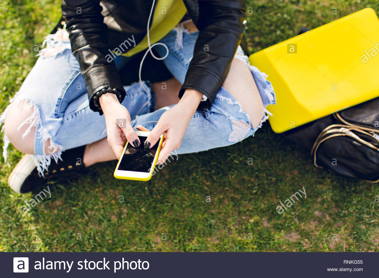 Phone in hands of a girl with ripped jeans sitting on grass, yellow laptop, black bag. View from above. - Stock Image