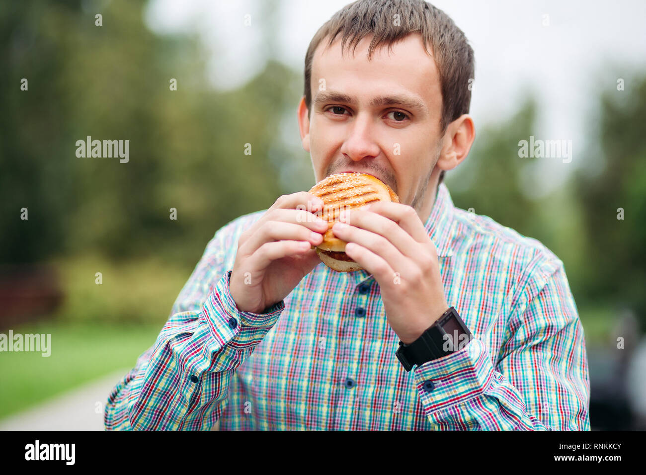 Man in checked shirt eating tasty burger outdoors. - Stock Image