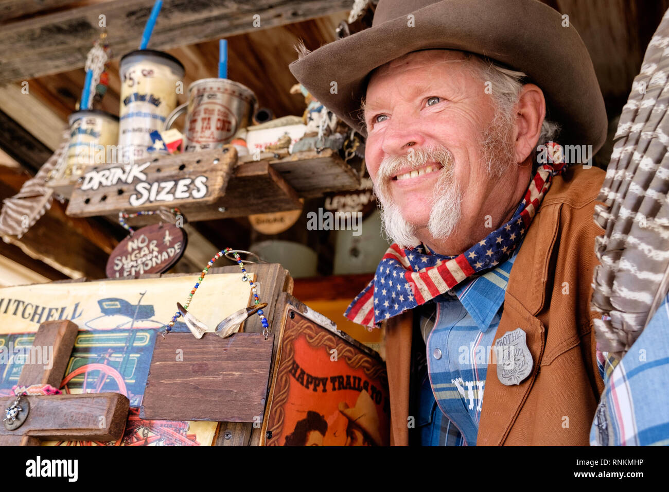 Smiling Texan Cowboy with cowboy hat, scarf & white horseshoe moustache at Wild West Soda market booth, Third Monday Trade Days Market. March 2018 - Stock Image