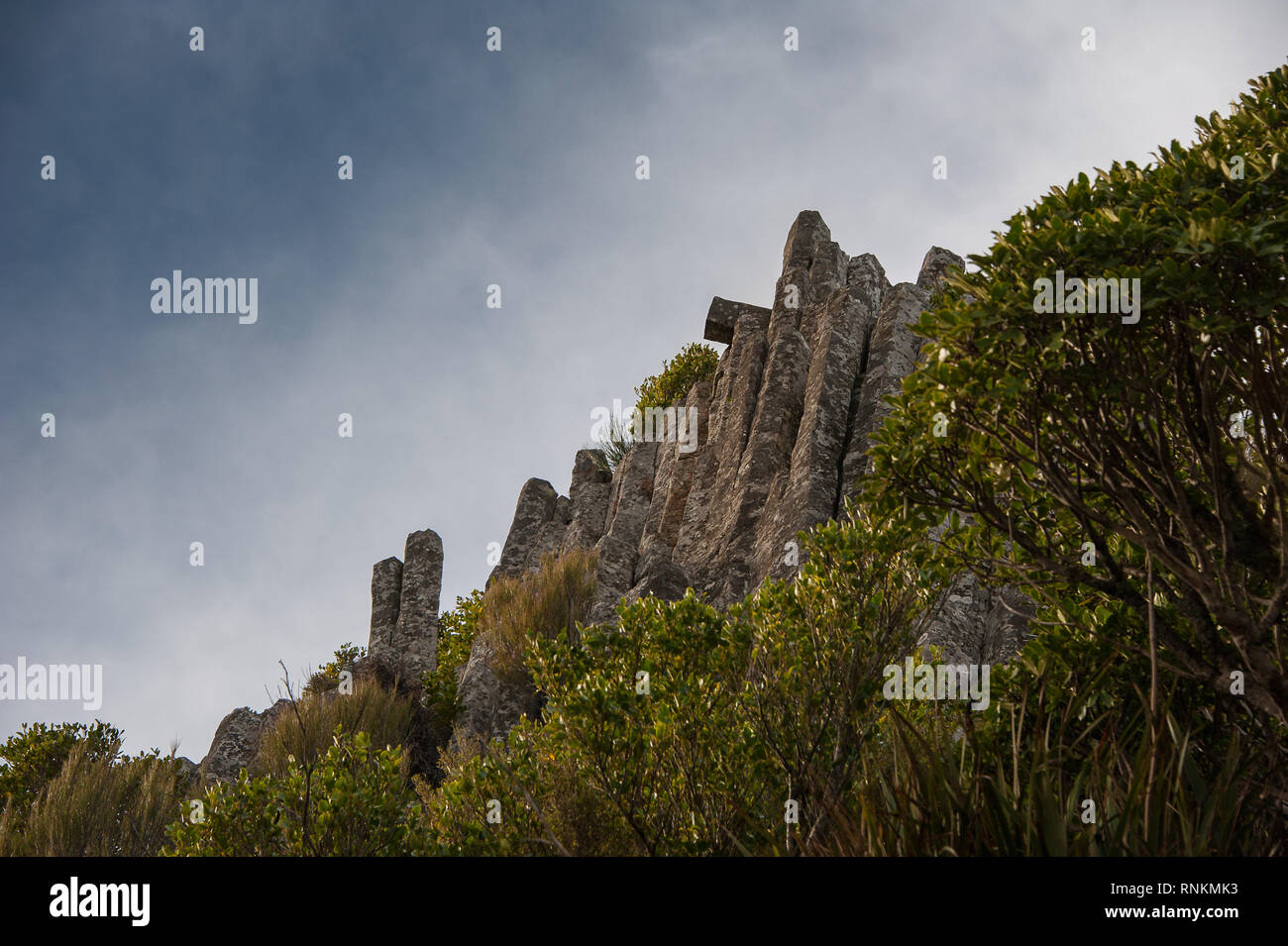The Organ Pipes, unique basalt columns Mt Cargill, Dunedin, New Zealand. Vertical pillars of volcanic rock stand against a blue, cloudy sky background - Stock Image