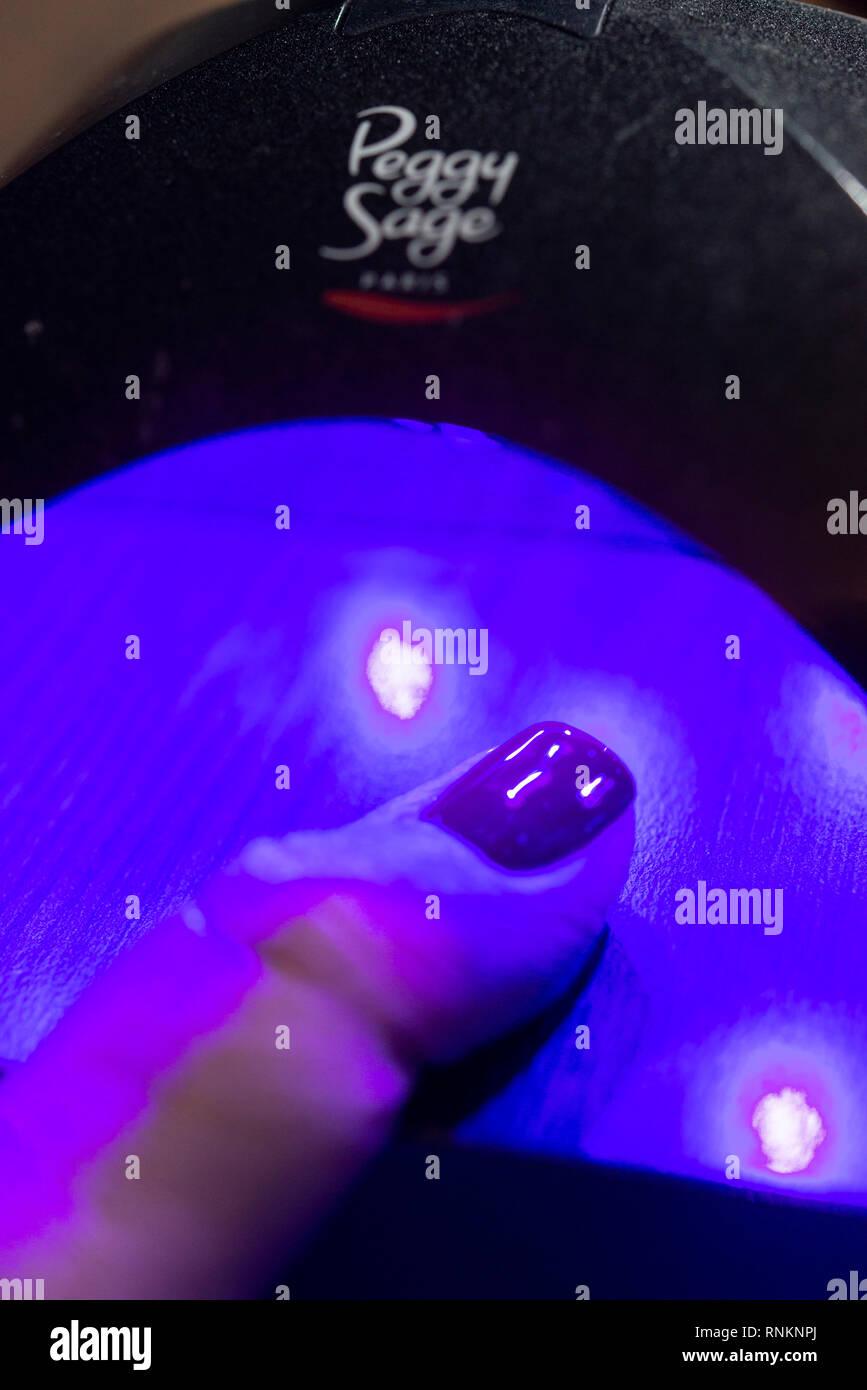 Nail technician: nail care and semi-permanent nail polish set to harden under a UV lamp - Stock Image