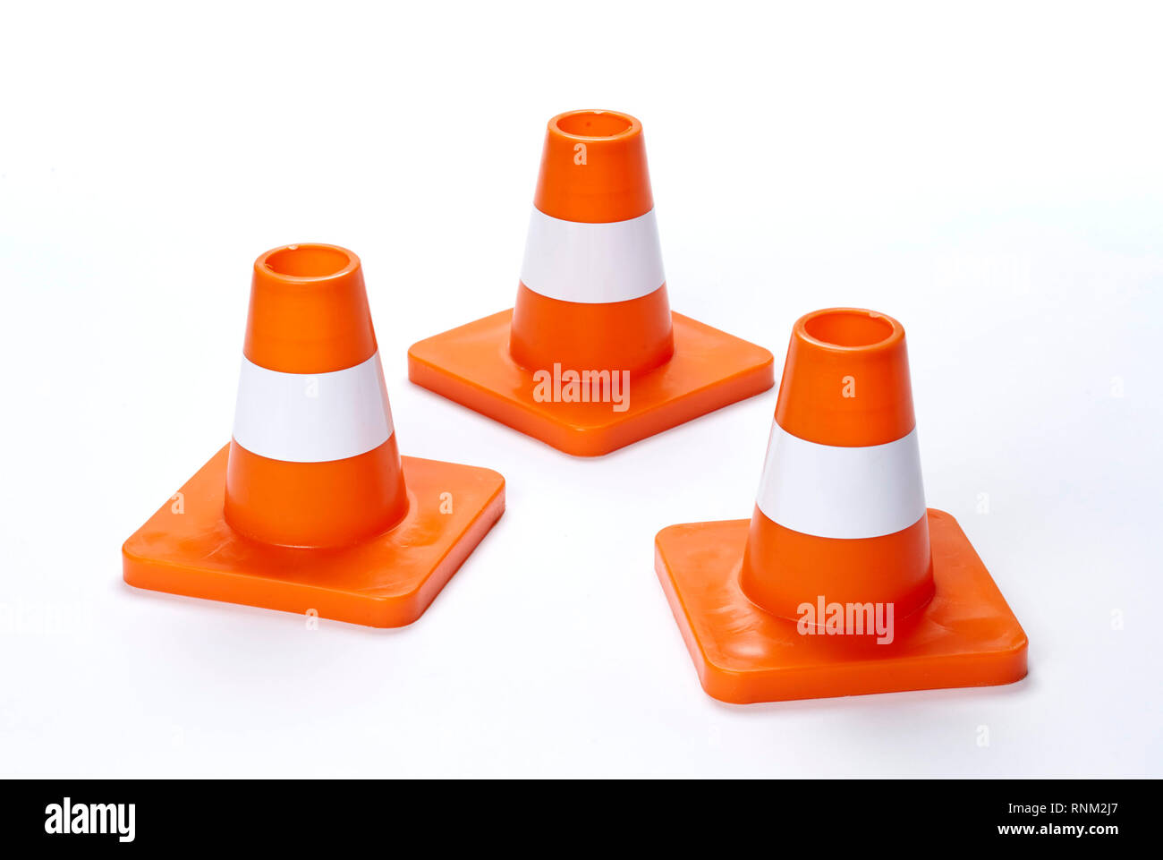 Three traffic cones. Studio picture against a white background - Stock Image