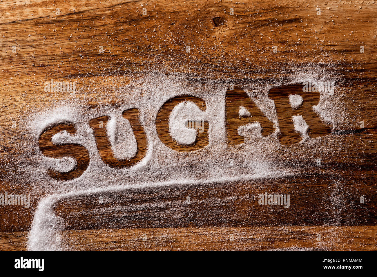 high angle view of a wooden table sprinkled with sugar where you can read the word sugar - Stock Image
