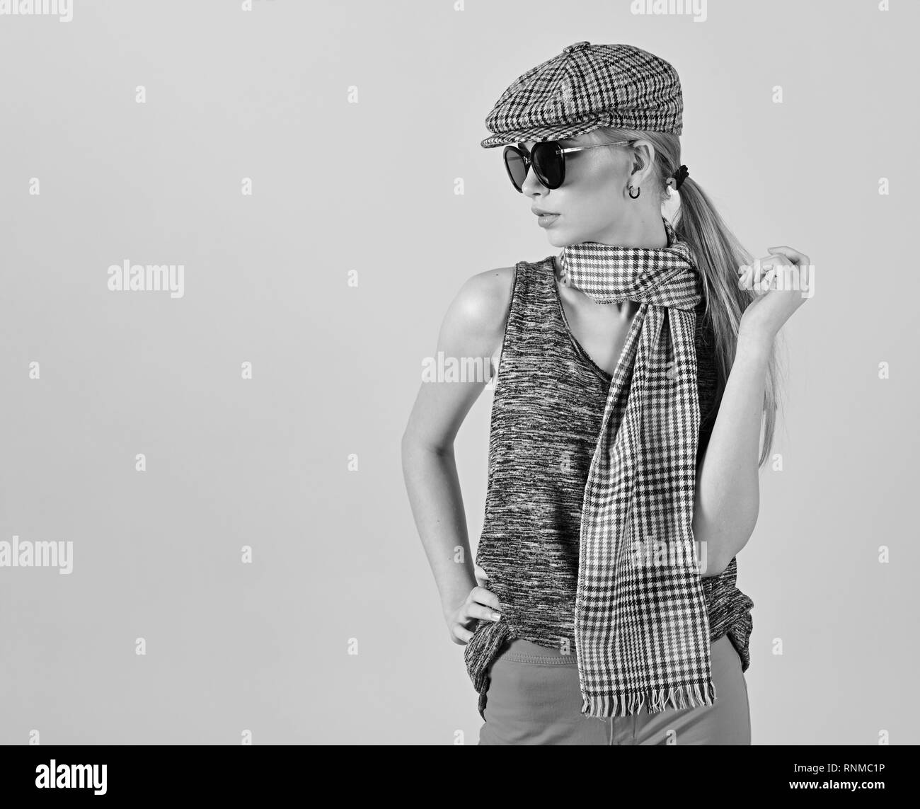 3129737ae0a Side view skinny blond model in tartan beige cap and scarf and black  sunglasses isolated on