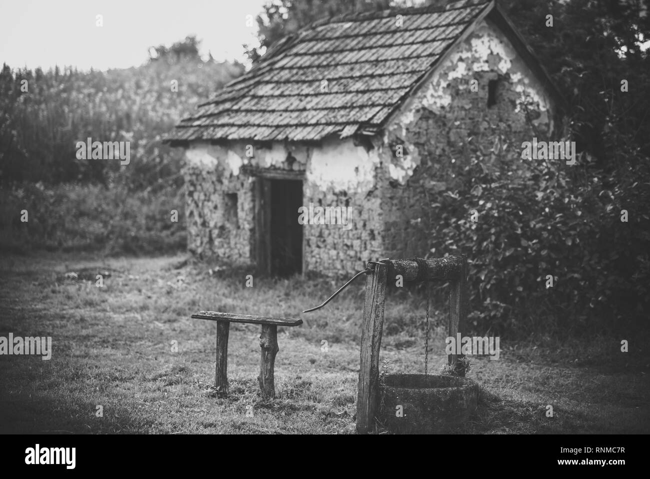 House barrack with old well in yard - Stock Image