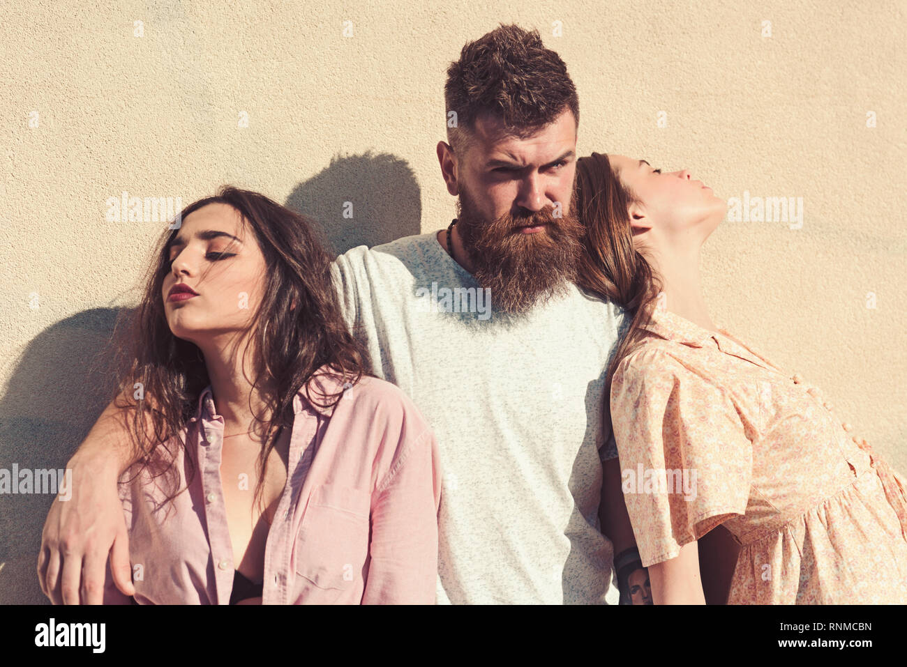 Man with beard hugs two ladies on hot sunny day. Threesome suffers of heat on summer day, wall on background. Girls turned to opposite sides while man - Stock Image