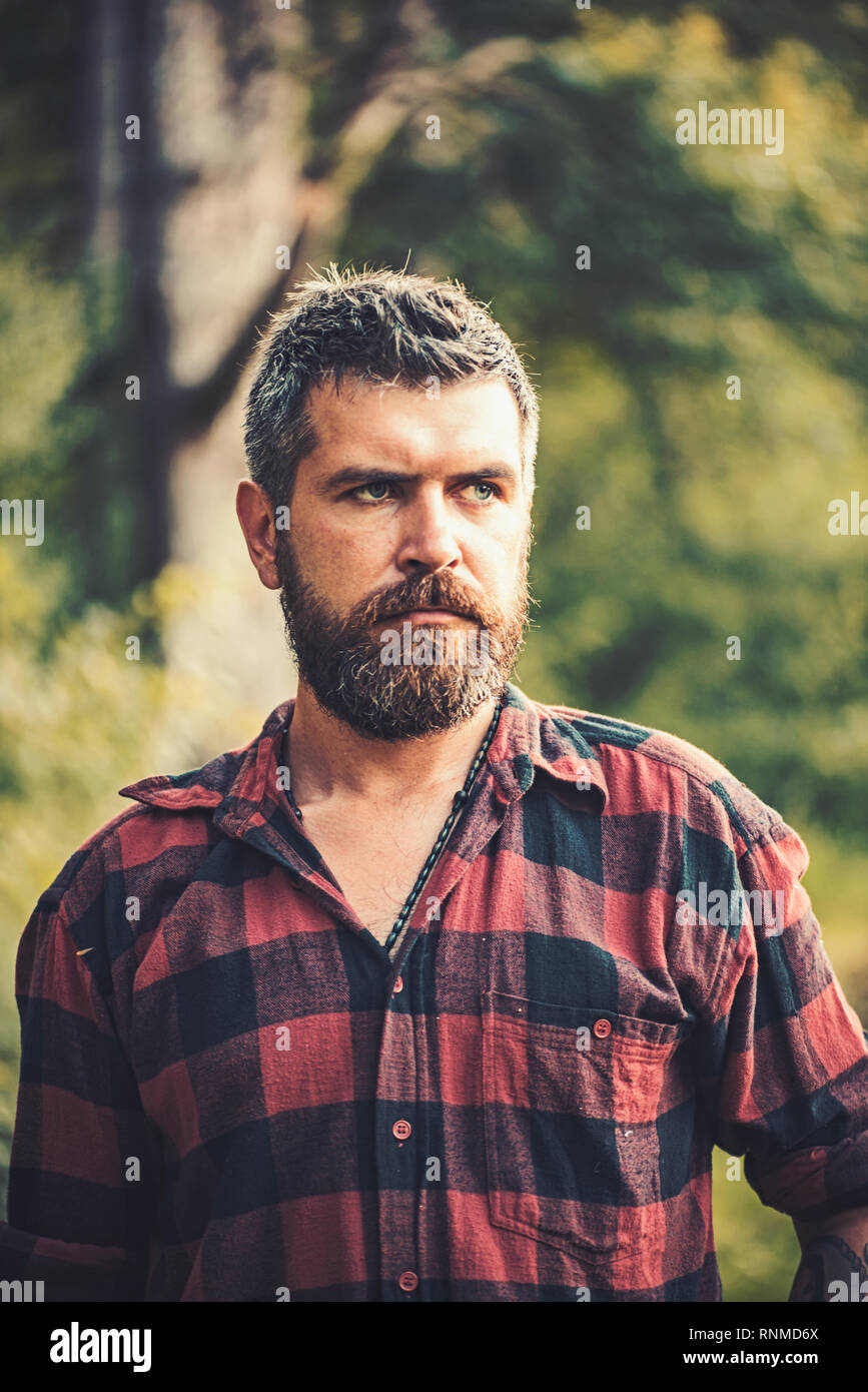 Brutal lumberjack wandering in wilderness. Ecologist exploring the forest. Environment and nature preserving concept - Stock Image