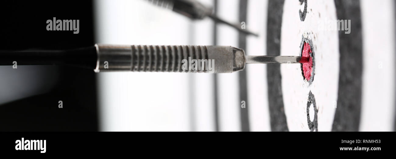The dart game sticks out in the center of the red Stock Photo