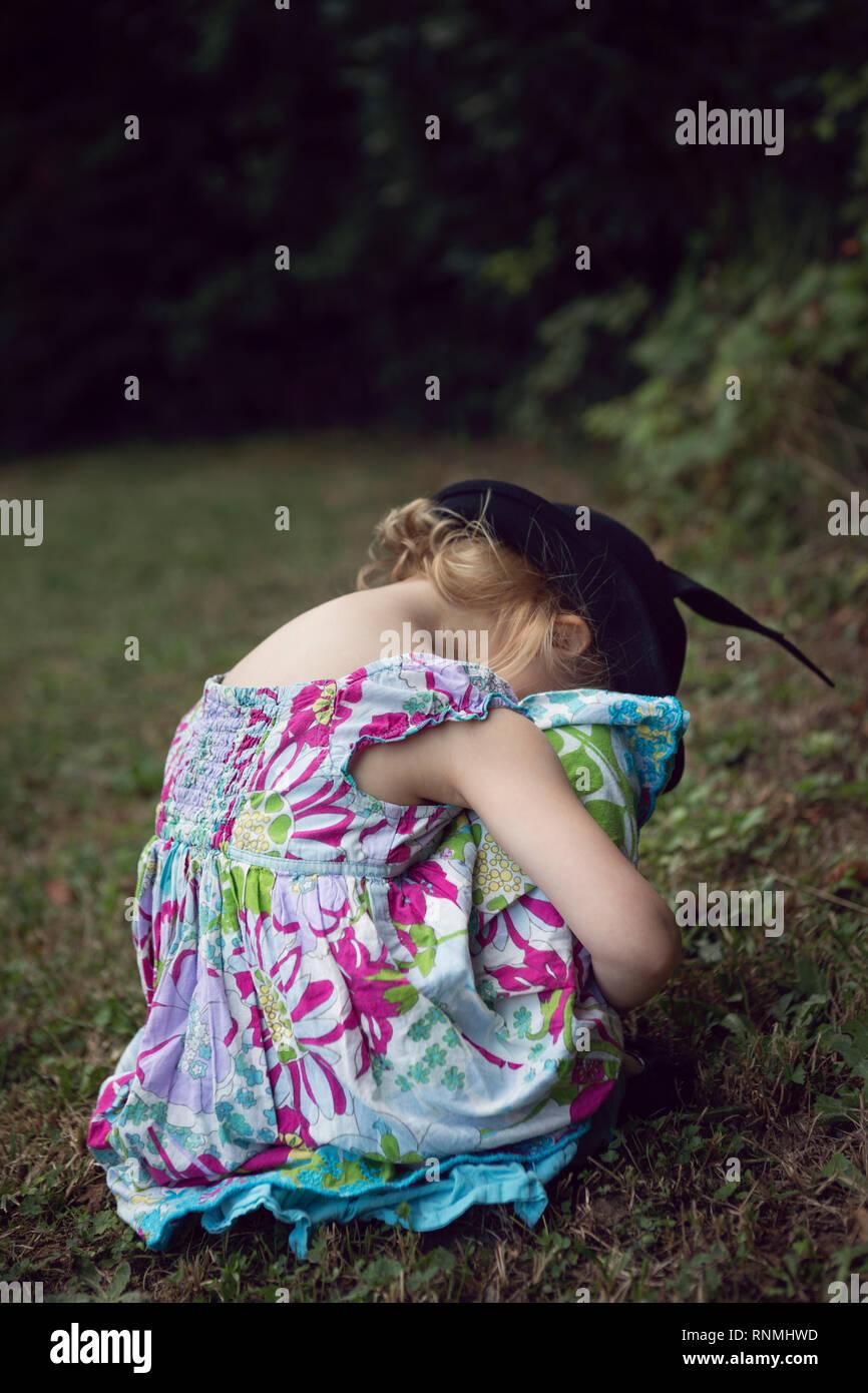 Little girl hiding her face and sulking - Stock Image