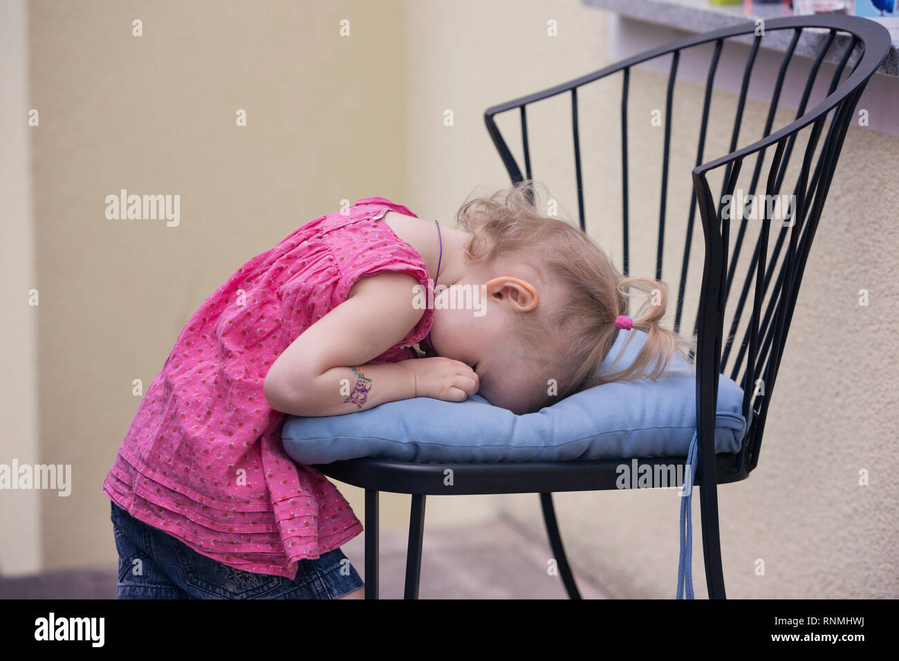 Little girl sulking and hiding her face on a chair cushion - Stock Image