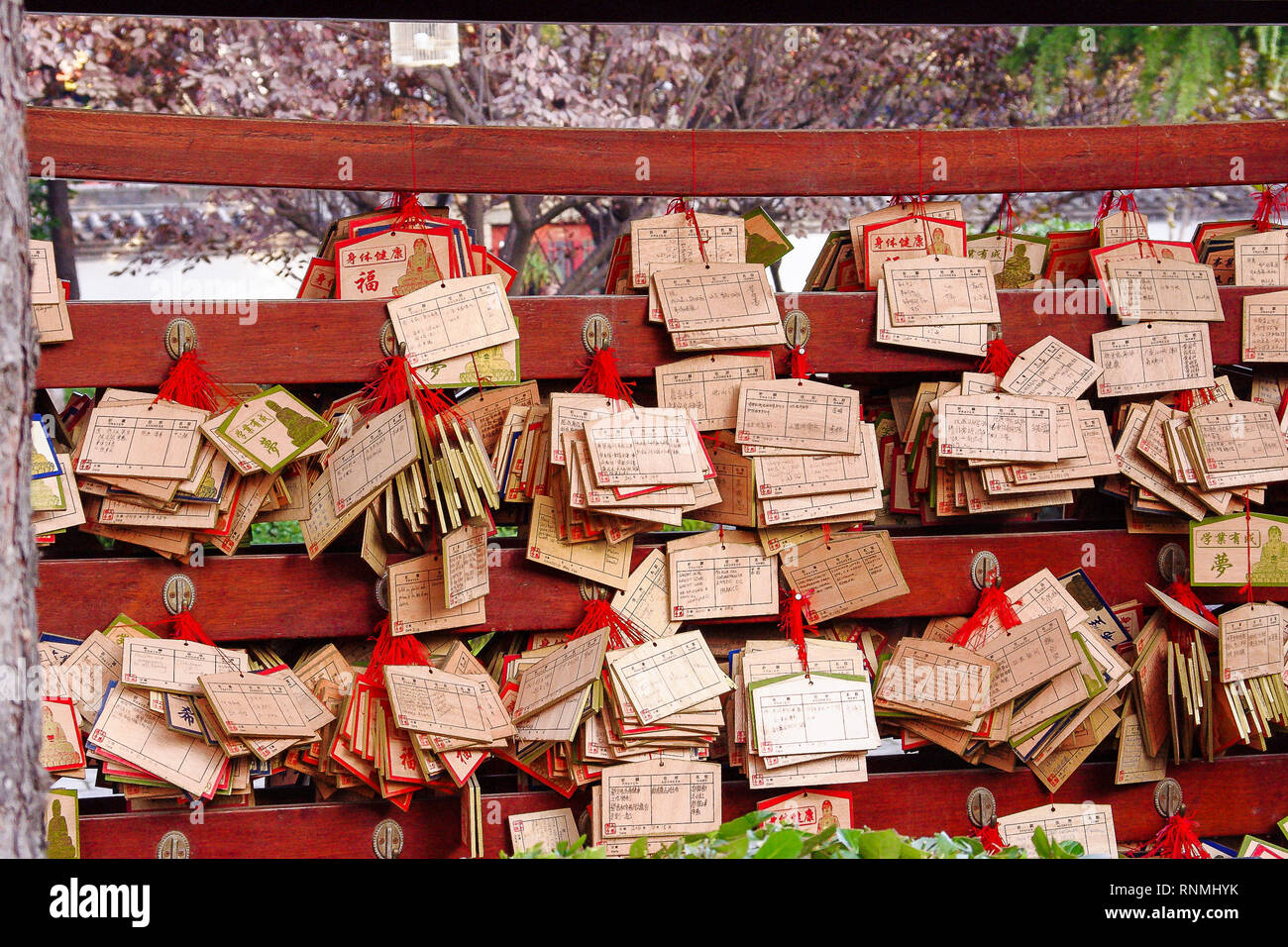 Traditional prayer cards hang outside Buddhist temple. Originating in Japan, Ema are wooden plaques, inscribed with wishes. They are later burned. - Stock Image
