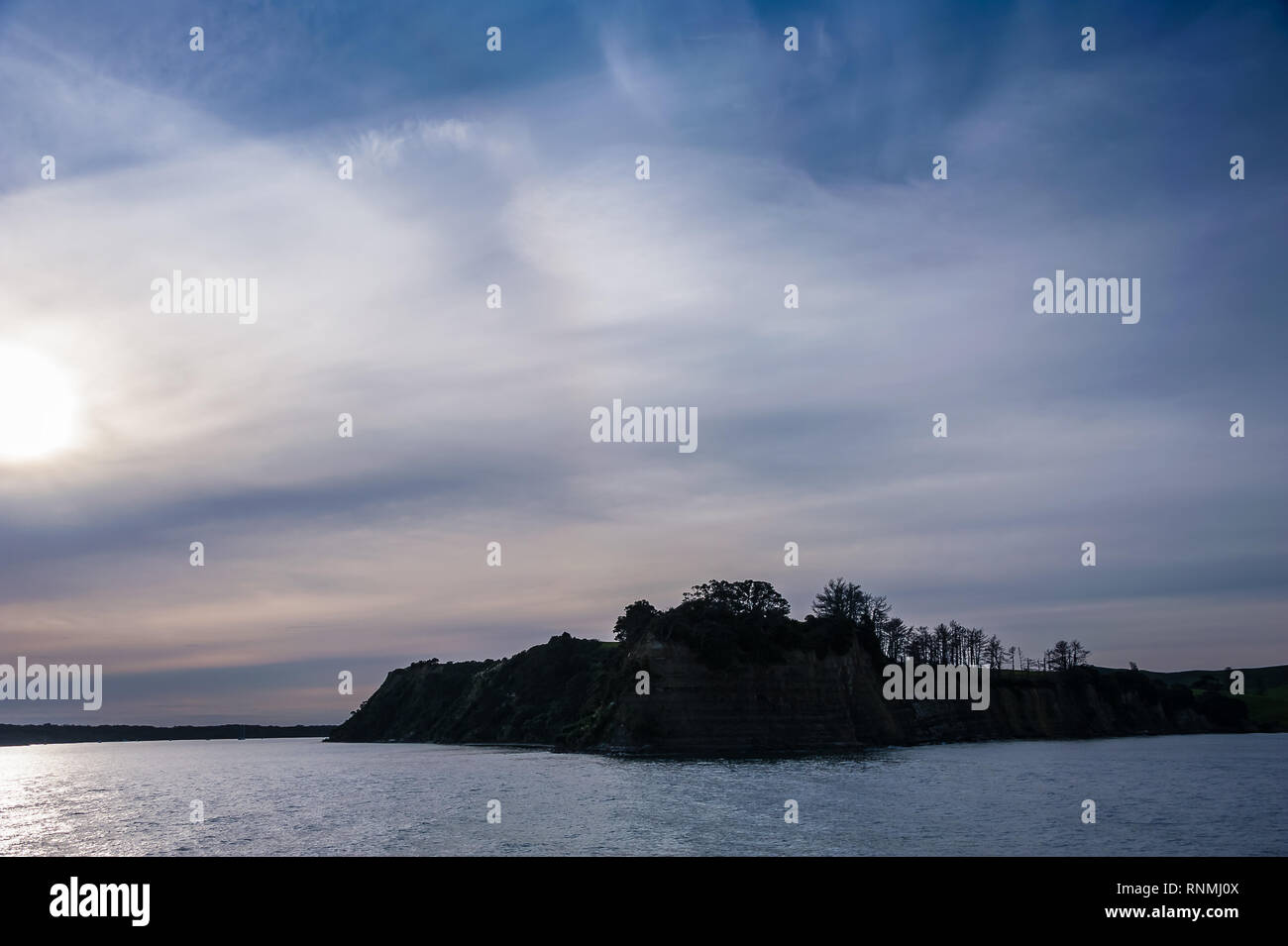 Moody sunset in the Hauraki Gulf, Waiheke to Auckland. Breathtaking landscape, headland silhouetted against setting sun. - Stock Image