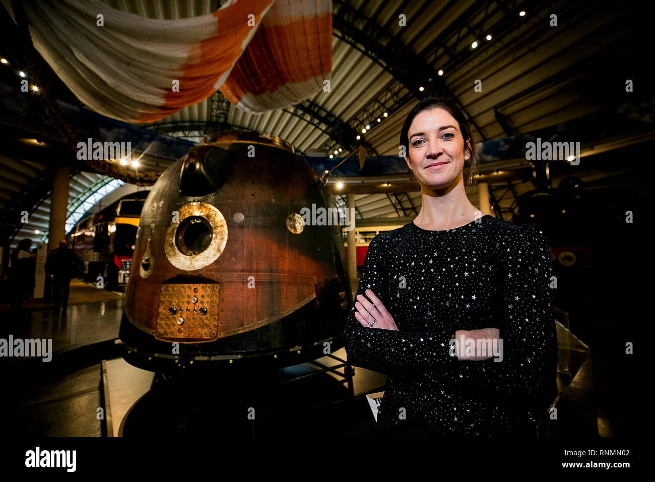 Dr. Norah Patten stands beside British astronaut Tim Peake's Soyuz TMA-19M capsule complete with equipped interior and char marks on its outer body from its re-entry into EarthÕs atmosphere, with the 25-metre diameter parachute used during it's high-speed descent back to Earth. The capsule and exhibition is viewable to the public at the Ulster Folk and Transport Museum in Cultra from February 20. - Stock Image