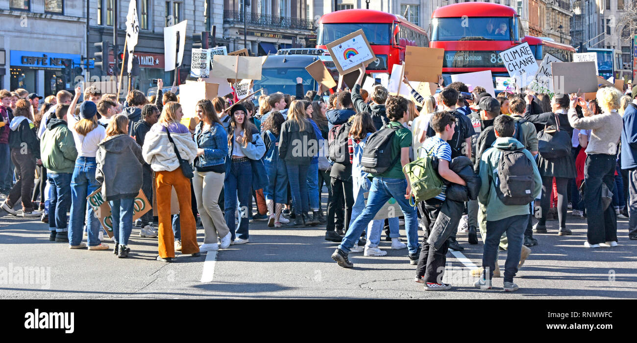 Group of teenagers school children kids miss school to strike & protest on climate change wave placard & chant blocking road traffic London England UK - Stock Image