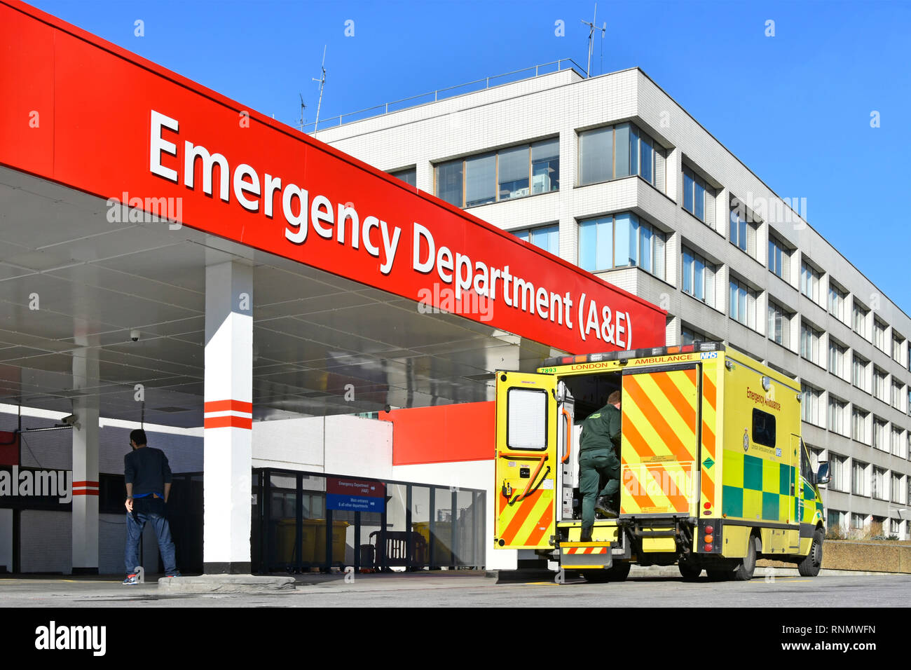 London NHS national health service ambulance & driver outside healthcare entrance hospital building A&E accident and emergency department England UK - Stock Image