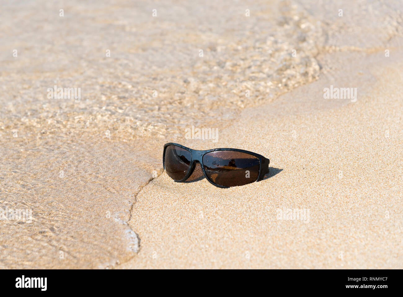Black sunglasess left in the sand on the beach - Stock Image