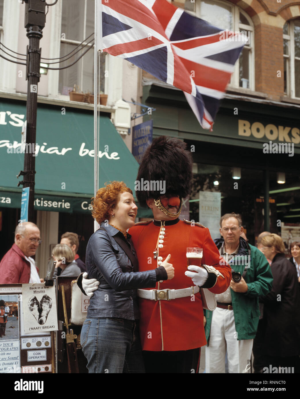 UK. England. Man dressed as a Coldstream Guard holding pint of beer and wearing red nose, posing with tourist for photograph in aid of Comic Relief. Stock Photo