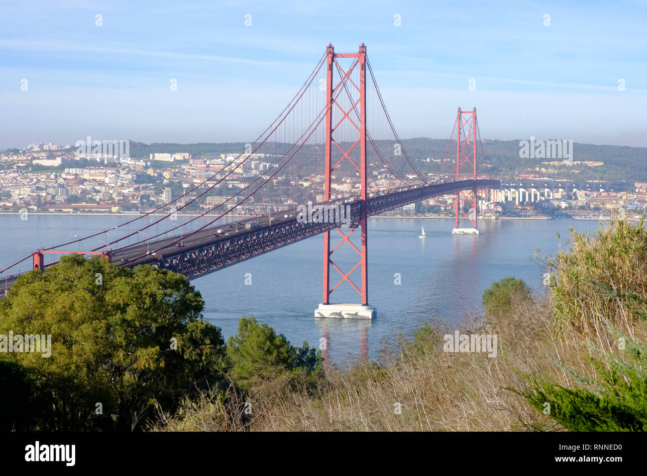 25 de Abril bridge (April 25 bridge) connects the city of Lisbon to Almada on the south bank crossing the river Tagus Stock Photo