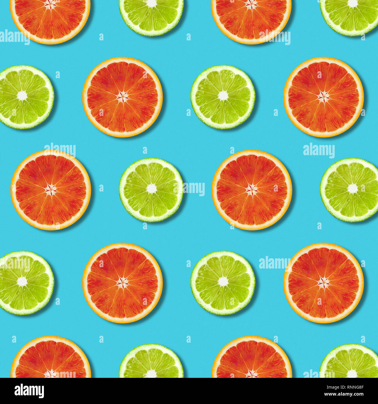 Vibrant red orange and green lime lemon slices pattern on turquoise color background. Minimal flat lay top view food texture Stock Photo
