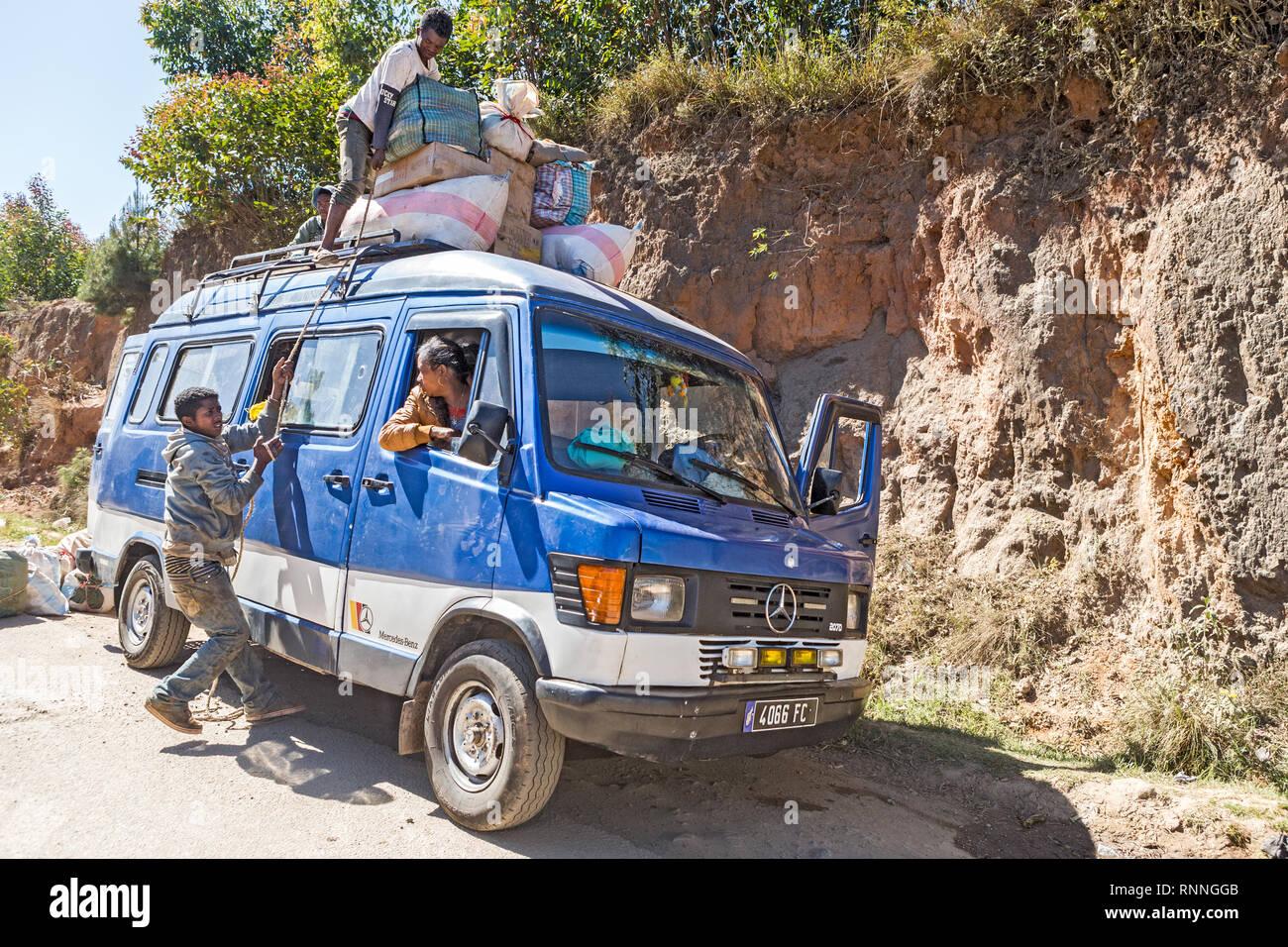 "Loading up ""mini-van"" bus service Views along N7 Ranomafana to Antsirabe Madagascar Stock Photo"