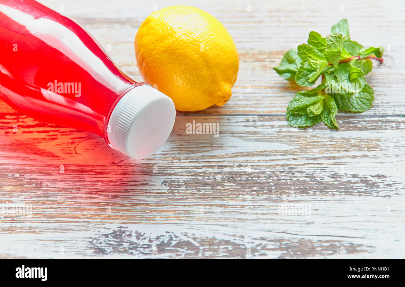 summer refreshing drink of berries in a plastic bottle on a wooden table. shut. place for text. empty space. - Stock Image