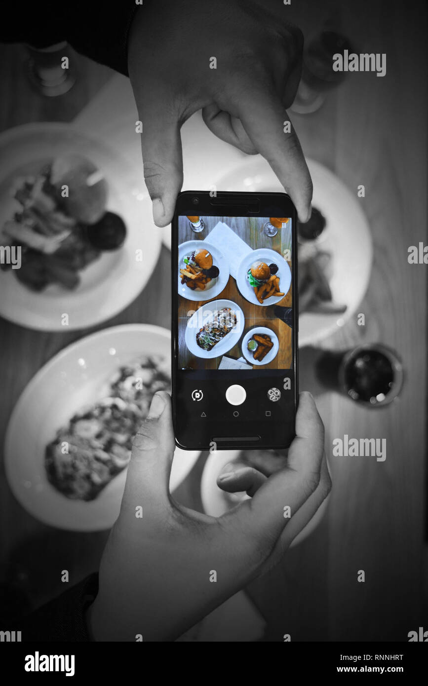 Adult male hands taking a photo of their meal on a table with a cell phone. Photo is taken from the top of the meal. - Stock Image