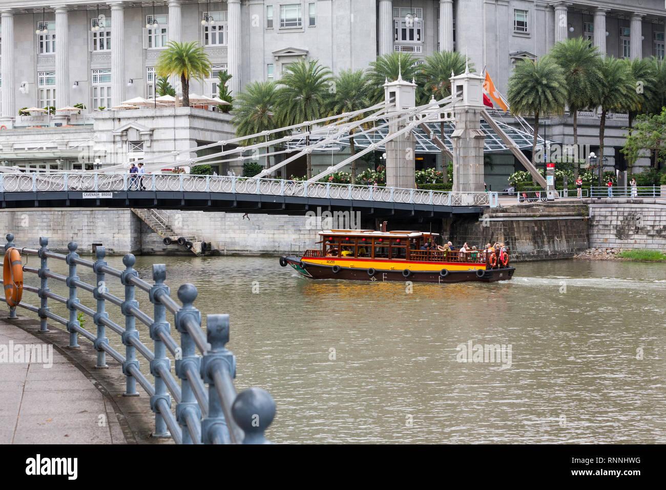 Singapore River Water Taxi Going under Cavenagh Bridge, Singapore. - Stock Image