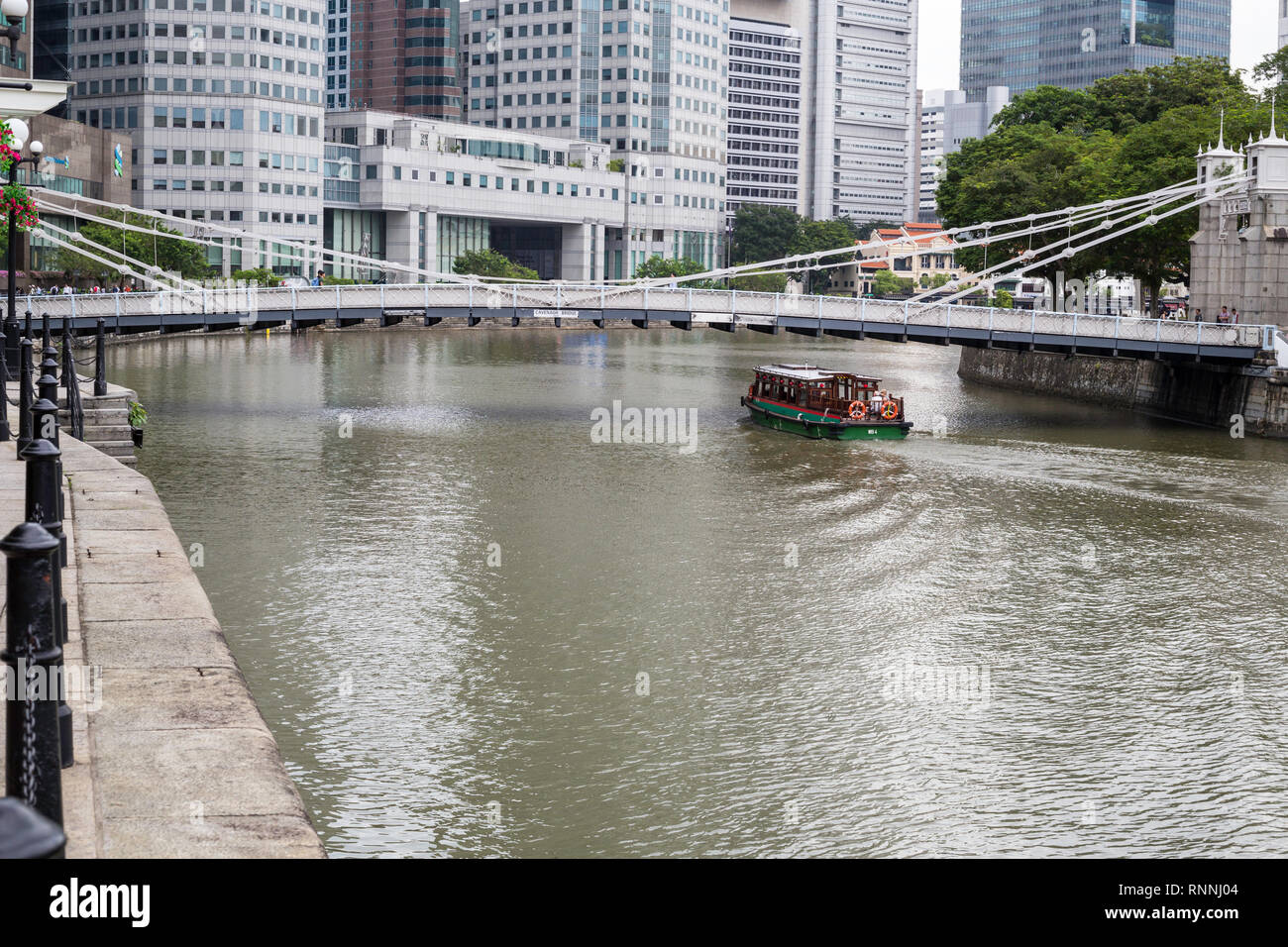 Water Taxi Passing under Cavenagh Bridge over Singapore River, 1870, Singapore. - Stock Image