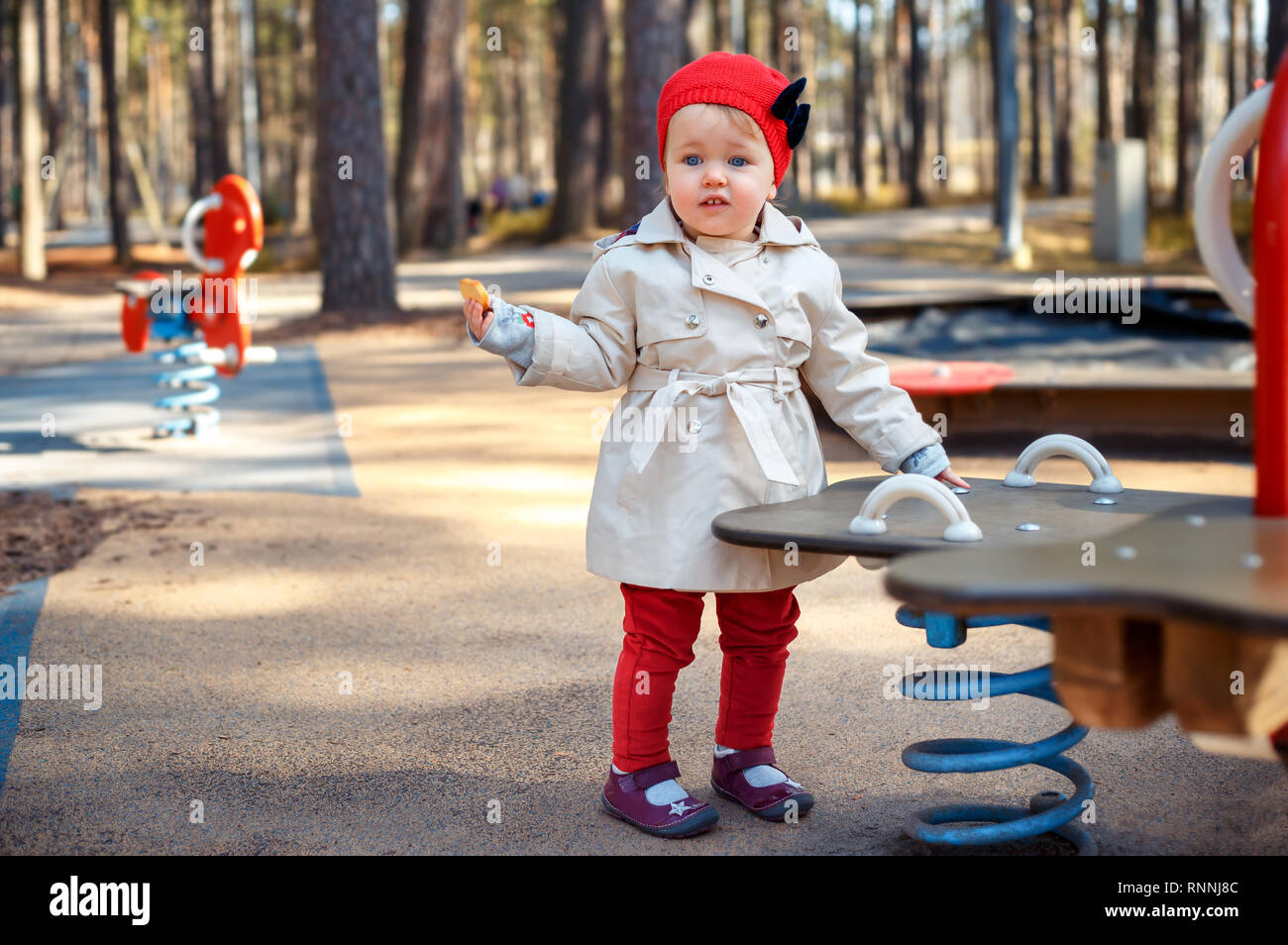 Sweet blond little toddler girl in beautiful beige trench coat and red cap plays outdoors at playground - Stock Image